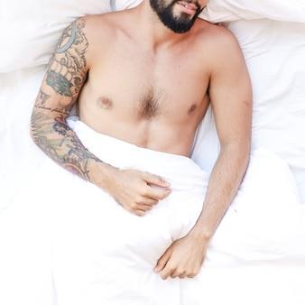 Vista dall'alto di un uomo senza camicia che dorme sul letto