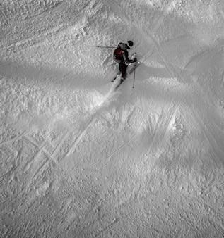 Vista dall'alto di un uomo solo con gli sci in inverno sulla montagna innevata.