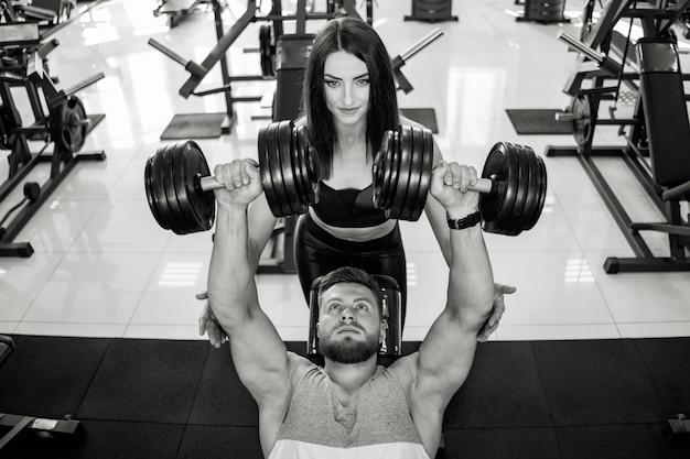 Vista dall'alto di una bella donna in abiti sportivi aiutare l'uomo forte a sollevare manubri. foto in bianco e nero di bella coppia nella palestra di sport che si esercita con le teste di legno.