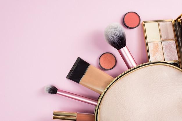 Vista dall'alto di una borsa per il trucco in pelle beige, con prodotti cosmetici di bellezza che si riversano su uno sfondo rosa pastello