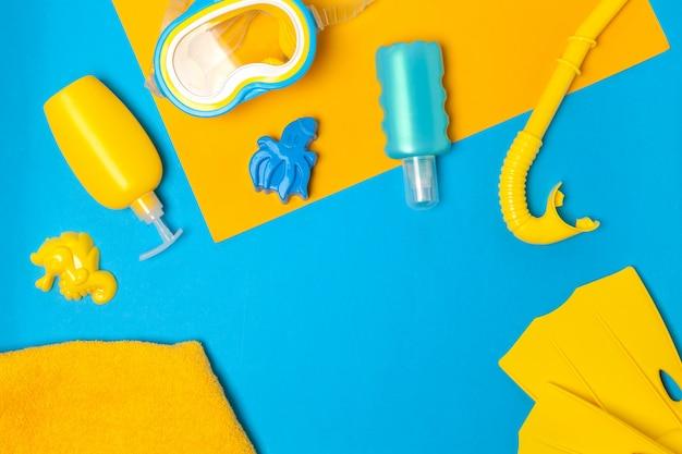Vista dall'alto di una composizione essenziale di spiaggia di giocattoli di plastica e attrezzatura per lo snorkeling