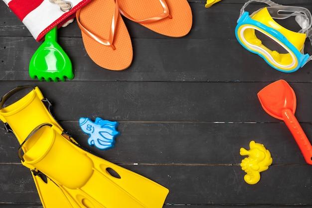 Vista dall'alto di una composizione essenziale spiaggia di giocattoli di plastica e attrezzature per lo snorkeling