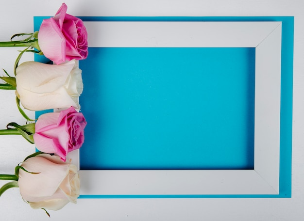 Vista dall'alto di una cornice vuota con rose bianche e rosa su sfondo blu con spazio di copia