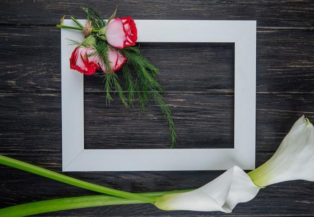 Vista dall'alto di una cornice vuota con rose rosse con finocchi e calle di colore bianco su fondo di legno scuro con spazio di copia