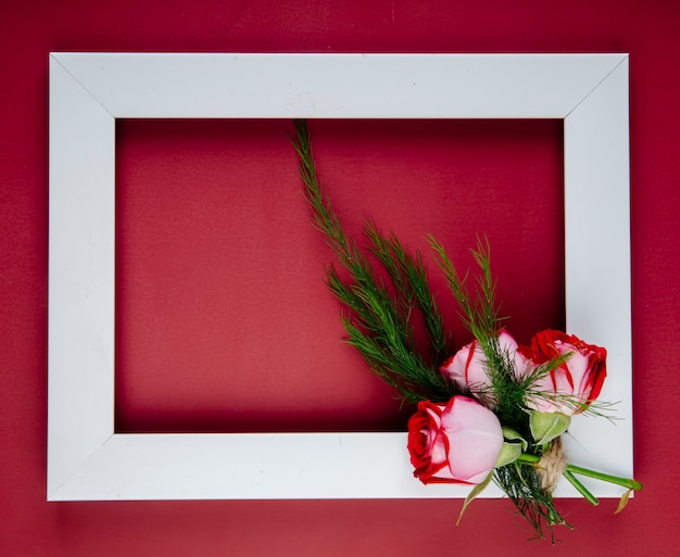 Vista dall'alto di una cornice vuota con un piccolo bouquet di rose di colore rosso con finocchio su sfondo rosso con spazio di copia