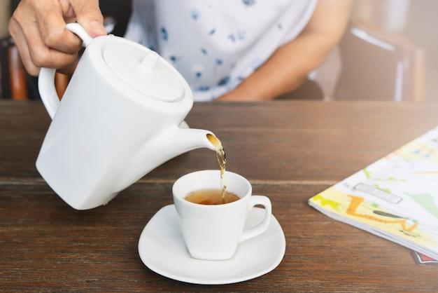 Vista dall'alto di una donna che versa il tè sulla tavola di legno