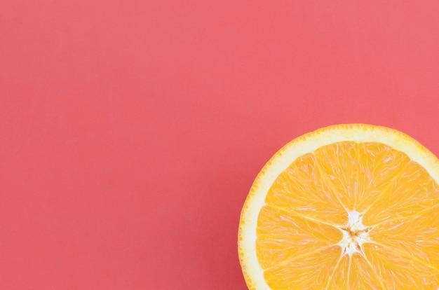 Vista dall'alto di una fetta di frutta arancione su sfondo luminoso in colore rosso.