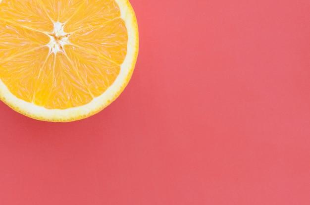 Vista dall'alto di una fetta di frutta arancione su sfondo luminoso in colore rosso