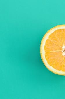 Vista dall'alto di una fetta di frutta arancione su sfondo luminoso in colore verde turchese. un'immagine di trama di agrumi saturi