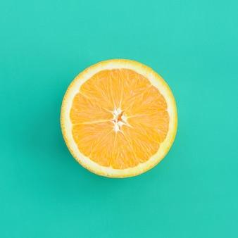 Vista dall'alto di una fetta di frutta arancione su sfondo luminoso in colore verde turchese