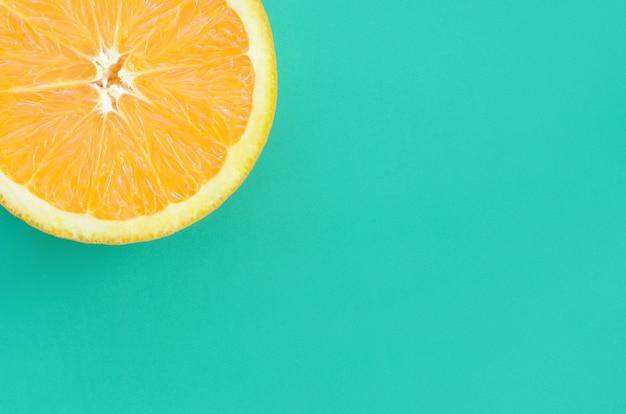 Vista dall'alto di una fetta di frutta arancione su sfondo luminoso in colore verde turchese.