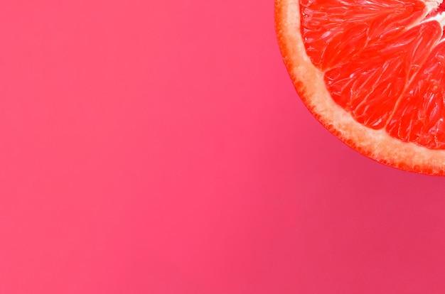 Vista dall'alto di una fetta di pompelmo su sfondo luminoso in colore rosa chiaro