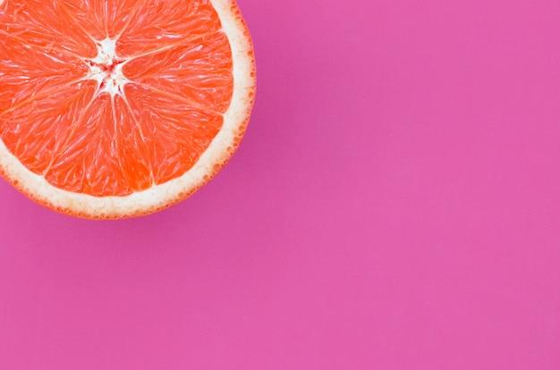 Vista dall'alto di una fetta di pompelmo su sfondo luminoso in colore viola
