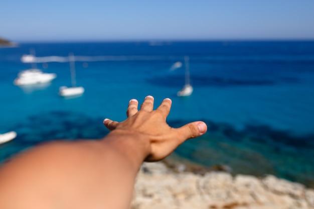 Vista dall'alto di una mano maschile diretta su un mar mediterraneo turchese e la spiaggia dell'isola di corsica sullo sfondo.