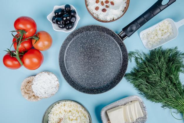 Vista dall'alto di una padella vuota e ricotta in una ciotola e torte di riso con crema di formaggio con aneto di pomodori freschi e olive in salamoia su blu
