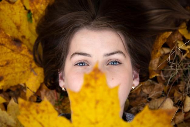 Vista dall'alto di una ragazza carina con gli occhi blu, che in autunno giace a terra e tiene una bella foglia d'acero gialla di fronte a lei.