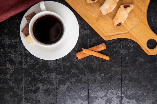 Vista dall'alto di una tazza di caffè con bastoncini di cannella al cioccolato e biscotti di farina su sfondo nero