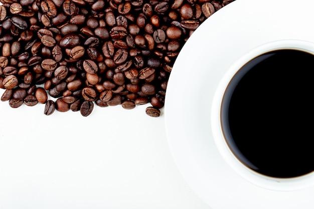 Vista dall'alto di una tazza di caffè con chicchi di caffè su sfondo bianco con spazio di copia