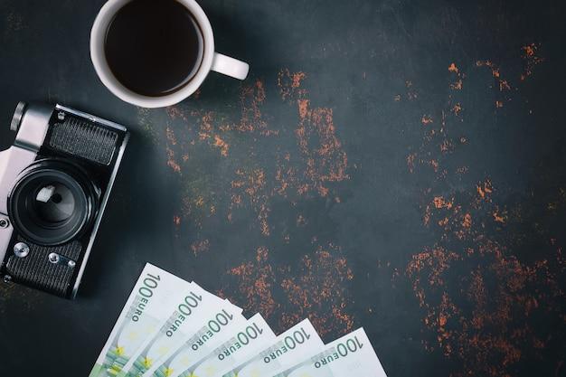 Vista dall'alto di una tazza di caffè con macchina da presa vintage e banconote in europa su sfondo di pietra arrugginita