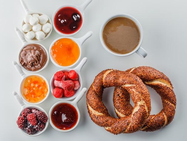 Vista dall'alto di una tazza di caffè con marmellate, lamponi, zucchero, cioccolato in tazze e bagel turco sulla superficie bianca
