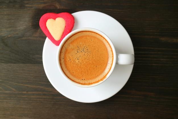 Vista dall'alto di una tazza di caffè espresso con biscotto a forma di cuore sul tavolo di legno