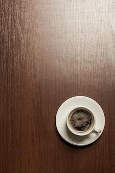 Vista dall'alto di una tazza di carta di caffè nero sul tavolo di superficie in legno