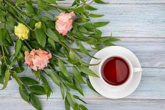 Vista dall'alto di una tazza di tè con bellissimi fiori e foglie su grigio