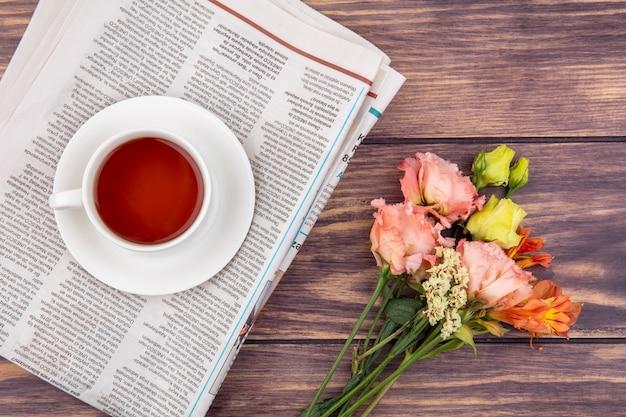 Vista dall'alto di una tazza di tè con meravigliosi fiori su legno