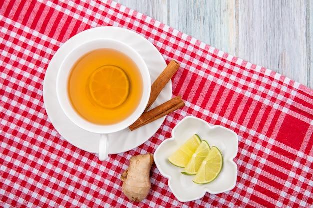 Vista dall'alto di una tazza di tè sul panno rosso controllato con bastoncini di cannella con fette di limone sulla ciotola bianca su legno grigio