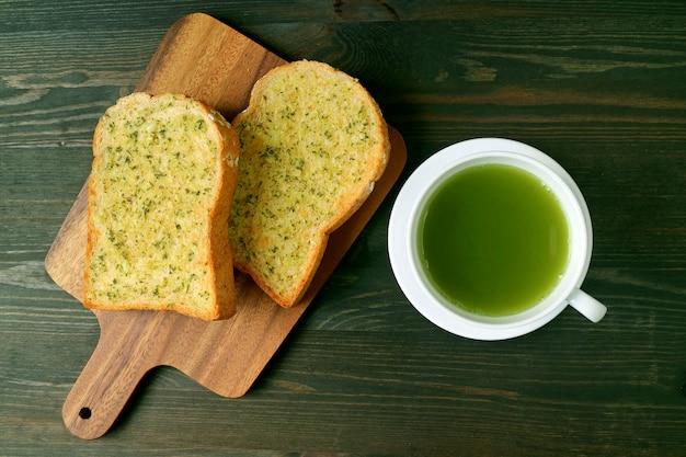 Vista dall'alto di una tazza di tè verde caldo e toast al burro all'aglio sul tavolo di legno marrone scuro