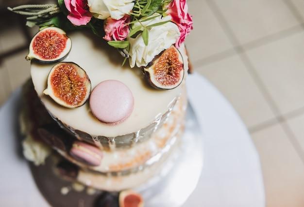 Vista dall'alto di una torta nuziale decorata con frutta di fico, macarons e fiori