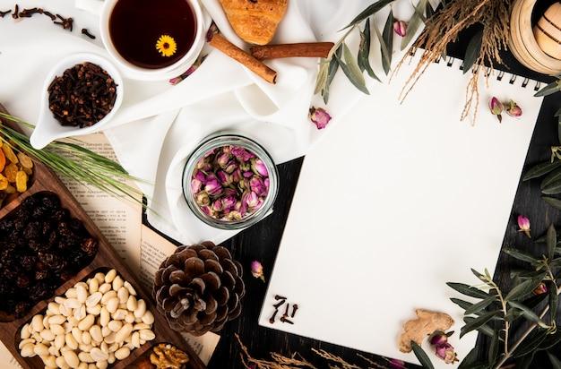 Vista dall'alto di uno sketchbook con boccioli di rosa tea in un barattolo di vetro, pigne, noci miste e brunch di alberi con foglie e una tazza di tè su legno nero