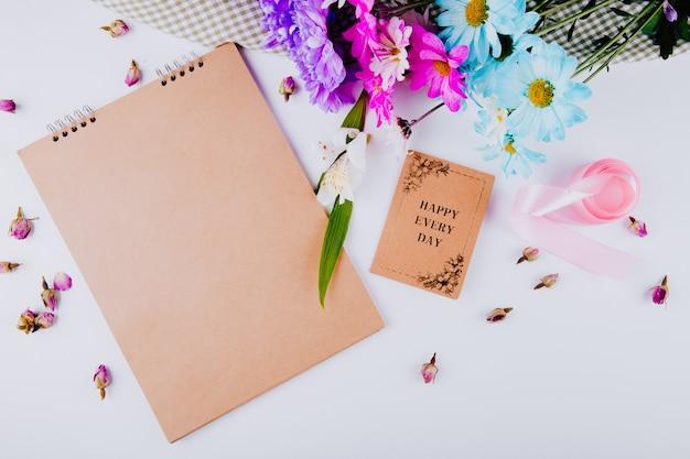 Vista dall'alto di uno sketchbook con una cartolina e bouquet di fiori di crisantemo colorato su sfondo bianco