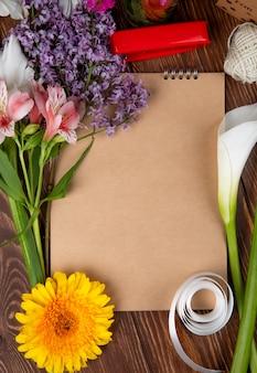 Vista dall'alto di uno sketchbook e bouquet di fiori primaverili di fiori e lillà rosa di alstroemeria su fondo di legno