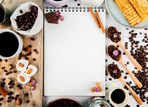 Vista dall'alto di uno sketchbook e chicchi di caffè in una ciotola di legno e cucchiai e con pezzi di cioccolato lokum e chicchi di caffè sparsi su fondo rustico