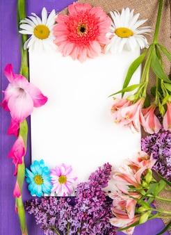 Vista dall'alto di uno sketchbook e fiori di colore rosa e viola gerbera lilla alstroemeria e fiori margherita vestirono su fondo in legno viola