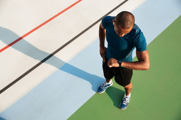 Vista dall'alto di uno sportivo africano, guardando il suo orologio da polso