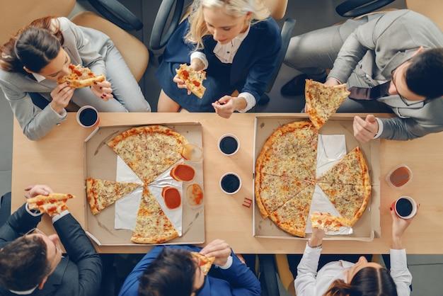 Vista dall'alto di uomini d'affari in abbigliamento formale seduto al tavolo e mangiare la pizza per il pranzo.