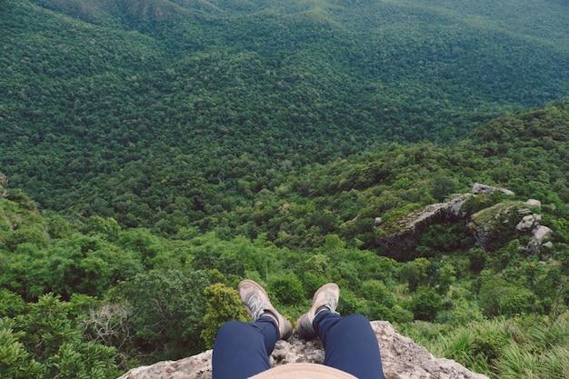 Vista dall'alto di uomini seduti sulla scogliera contro la montagna e l'albero
