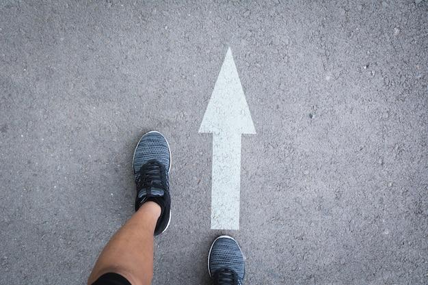 Vista dall'alto di uomo che indossa scarpe scegliendo un modo segnato con frecce bianche.
