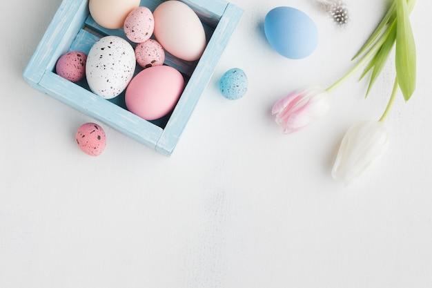 Vista dall'alto di uova colorate per pasqua con tulipani