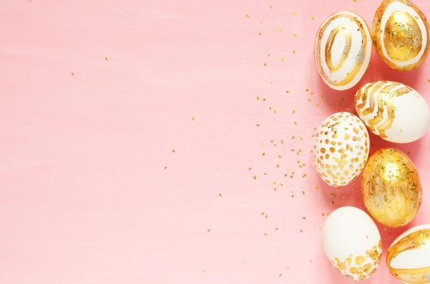 Vista dall'alto di uova di pasqua colorate con vernice dorata in diversi modelli.