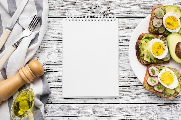 Vista dall'alto di uova e avocado panini sulla piastra con il taccuino