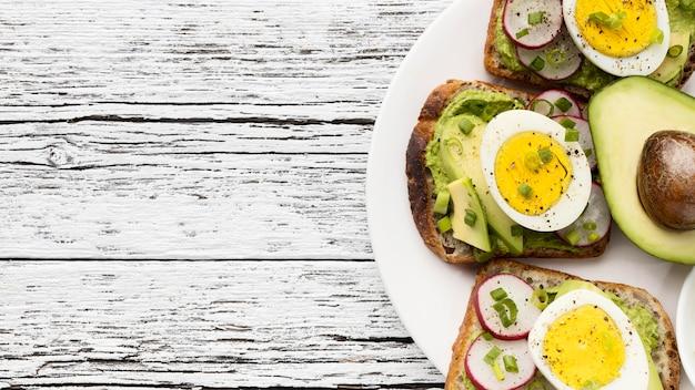 Vista dall'alto di uova e avocado panini sulla piastra con spazio di copia