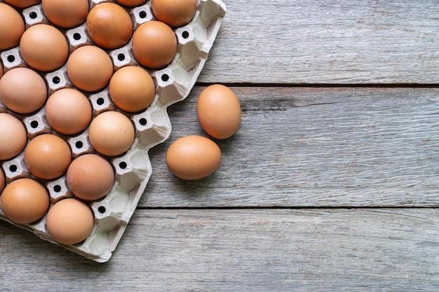 Vista dall'alto di uova nel vassoio della carta su sfondo di legno