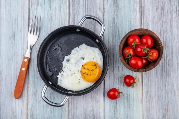 Vista dall'alto di uovo fritto in padella con forchetta e ciotola di pomodoro su legno