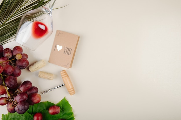 Vista dall'alto di uva fresca, piccola cartolina, vite bottiglia e un bicchiere di vino sdraiato sul tavolo bianco con spazio di copia