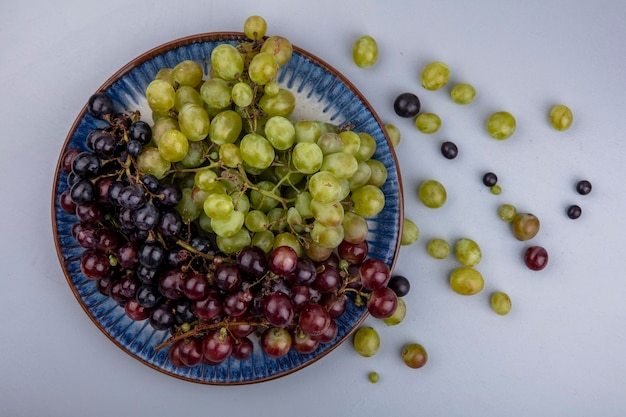 Vista dall'alto di uva nel piatto e acini d'uva su sfondo grigio