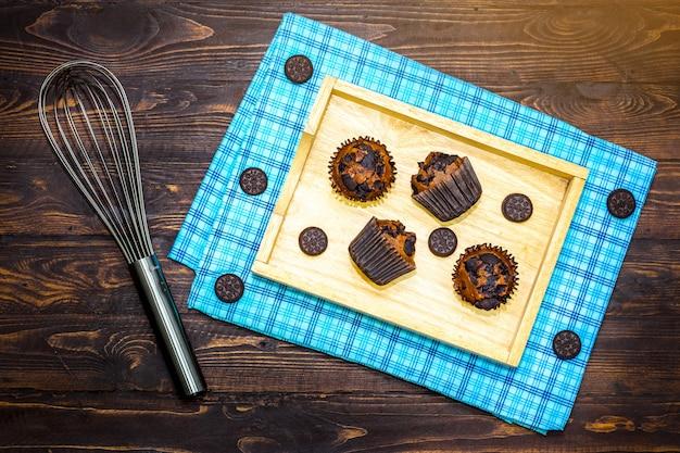 Vista dall'alto di vanila, muffin al cioccolato in titolare di carta cupcake con cookie sul tovagliolo di legno
