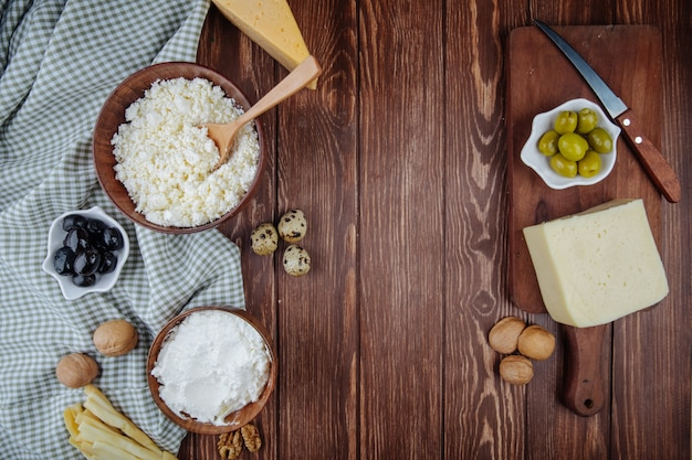 Vista dall'alto di vari formaggi e ricotta in una ciotola con noci, uova di quaglia e olive in salamoia sul tagliere di legno con un coltello sul tavolo rustico